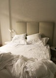 An unmade bed in a hotel room Stock Photos