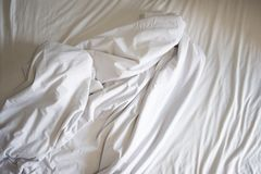 Unmade bed sheet of the crease and white blanket in the bedroom after sleep on top view Wrinkled fabric. Unmade bed sheet of the crease and white blanket in the royalty free stock photo