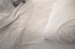 An unmade bed with white linens Stock Photos