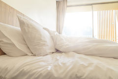 Unmade bed with white pillow Stock Photography