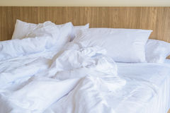 Unmade bed with white pillow Stock Photos