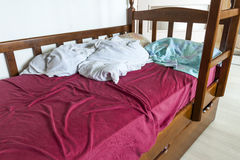 Unmade child bed with crumpled red and white bed linens and pill. Ow Royalty Free Stock Photo