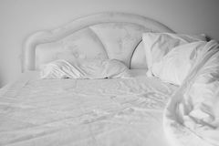 Unmade comfortable bed is strewn with white pillows. Royalty Free Stock Photo