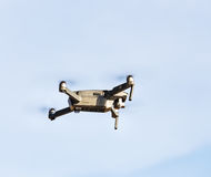 Unmanned aerial vehical with video camera hovers in the air. Thi Stock Image