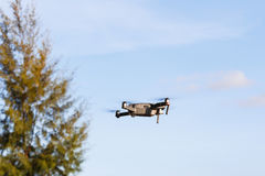 Unmanned aerial vehical with video camera hovers in the air. Thi Royalty Free Stock Images