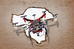 Unmanned aerial vehicle drone breaking through wall. Photo of an unmanned aerial vehicle drone flying through hole in brick wall stock images