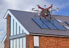 Unmanned aerial vehicle drone surveying home roof repairs. Photo of an unmanned aerial vehicle drone being used to survey the roof of a home for damage repairs royalty free stock photography