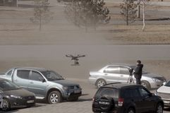 Unmanned aerial vehicle - quad copter with a camera and video broadcast is controlled by a man in a car parking in the city royalty free stock image
