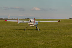 Unmanned aerial vehicle UAV on grass runway. White Unmanned aerial vehicle UAV on grass runway Stock Photos