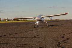 Unmanned aerial vehicle UAV starts from the asphalt runway. White Unmanned aerial vehicle UAV starts from the asphalt runway Stock Photos