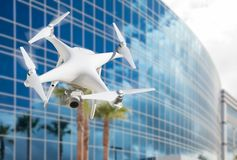 Unmanned Aircraft System UAS Quadcopter Drone Near Office Building. Unmanned Aircraft System UAS Quadcopter Drone In The Air Near Corporate Building Royalty Free Stock Images