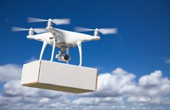 Unmanned Aircraft System UAS Quadcopter Drone Carrying Blank Box. Unmanned Aircraft System UAS Quadcopter Drone Carrying Blank Package In The Air Stock Image