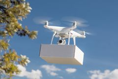 Unmanned Aircraft System UAS Quadcopter Drone Carrying Blank Box. Unmanned Aircraft System UAS Quadcopter Drone Carrying Blank Package In The Air Royalty Free Stock Photos