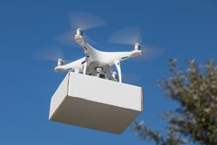 Unmanned Aircraft System UAS Quadcopter Drone Carrying Blank Box. Unmanned Aircraft System UAS Quadcopter Drone Carrying Blank Package In The Air Royalty Free Stock Photography