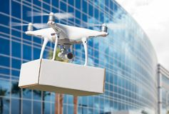 Unmanned Aircraft System UAS Quadcopter Drone Carrying Blank Package. Near Corporate Building Royalty Free Stock Photo