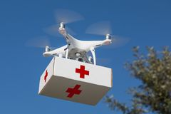 Unmanned Aircraft System UAS Quadcopter Drone Carrying First Aide Kit. Unmanned Aircraft System UAS Quadcopter Drone Carrying First Aid Package In The Air stock photography