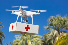 Unmanned Aircraft System UAS Quadcopter Drone Carrying First Aide Kit. Unmanned Aircraft System UAS Quadcopter Drone Carrying First Aid Package Over Tropical Royalty Free Stock Images