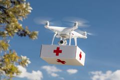 Unmanned Aircraft System UAS Quadcopter Drone Carrying First Aide Kit. Unmanned Aircraft System UAS Quadcopter Drone Carrying First Aid Package In The Air Stock Photos