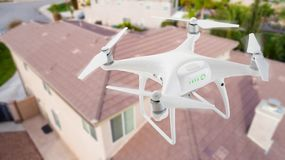 Unmanned Aircraft System UAV Quadcopter Drone In The Air Over. House Inspecting the Roof Royalty Free Stock Image