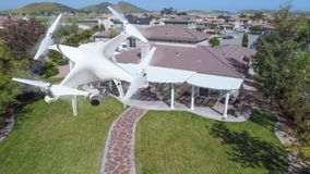 Unmanned Aircraft System UAV Quadcopter Drone In The Air Over. Houses Royalty Free Stock Image