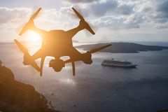 Unmanned Aircraft System UAV Quadcopter Drone In The Air At Su. Nset Over The Greek Isles Stock Photography