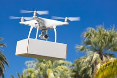Unmanned Aircraft System UAV Quadcopter Drone Carrying Blank Box. Unmanned Aircraft System UAV Quadcopter Drone Carrying Blank Package Over Tropical Terrain royalty free stock image