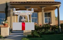 Unmanned Aircraft System UAV Quadcopter Drone Delivering Gift. Unmanned Aircraft System UAV Quadcopter Drone Delivering Box With Red Ribbon To Home royalty free stock photos