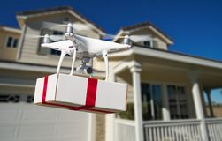 Unmanned Aircraft System UAV Quadcopter Drone Delivering Gift. Unmanned Aircraft System UAV Quadcopter Drone Delivering Box With Red Ribbon To Home stock photo