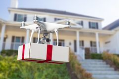 Unmanned Aircraft System UAV Quadcopter Drone Delivering Gift. Unmanned Aircraft System UAV Quadcopter Drone Delivering Box With Red Ribbon To Home stock photos