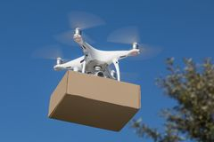 Free Unmanned Aircraft System UAV Quadcopter Drone Delivering Package Stock Photos - 153690083