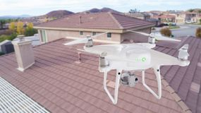 Unmanned Aircraft System UAV Quadcopter Drone Over Homes. Unmanned Aircraft System UAV Quadcopter Drone In The Air Over House Inspecting the Roof stock photos