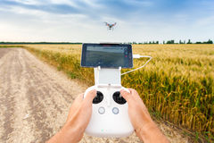 Unmanned copter. Man controls quadrocopter flight. Demonstration of unmanned copter. Man controls quadrocopter flight. Flying the copter over a field of wheat Royalty Free Stock Photos