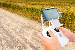 Unmanned copter. Man controls quadrocopter flight. Demonstration of unmanned copter. Man controls quadrocopter flight. Flying the copter over a field of wheat Stock Images
