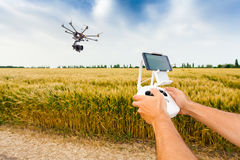 Unmanned copter. Man controls quadrocopter flight. Demonstration of unmanned copter. Man controls quadrocopter flight. Flying the copter over a field of wheat Royalty Free Stock Images