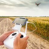 Unmanned copter. Man controls quadrocopter flight. Demonstration of unmanned copter. Man controls quadrocopter flight. Flying the copter over a field of wheat stock photography