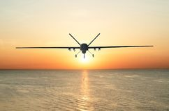 Unmanned military drone patrols the territory at sunset, flying above water surface. The view is straight ahead. Unmanned military drone patrols the territory stock photography
