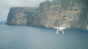 Unmanned spy scout in flight over the sea and mountains. Flight of a drone against the background of rocks and the sea stock footage