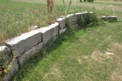 Light gray rough-hewn drystone retaining wall. Unmortared, drystone retaining wall made of massive rectangular blocks of light gray rough-hewn stone, with Stock Photo