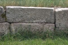 Rough-hewn drystone blocks used in a retaining wall. Unmortared, stacked drystone rectangular blocks of rough-hewn stone that form part of a decorative retaining Stock Photo