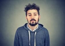 Unmotivated gnuśny młody człowiek na szarość fotografia royalty free