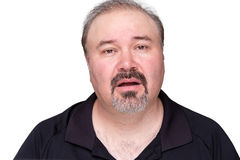 Unmotivated lethargic middle-aged man. With a goatee beard looking a the camera with a dim-witted expression and his mouth ajar, isolated on white Royalty Free Stock Photos