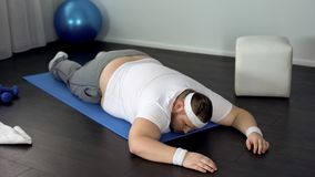 Unmotivated mężczyzny lying on the beach na macie, daje w górę skołowany mięśni trenować podczas fotografia royalty free