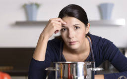 Unmotivated woman preparing the dinner. Unmotivated attractive young woman preparing the dinner leaning on the hob eyeing the camera with a listless glum Stock Photography
