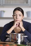 Unmotivated woman preparing the dinner. Unmotivated attractive young woman preparing the dinner leaning on the hob eyeing the fresh vegetables with a listless Stock Image