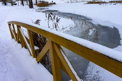 Unmoving frozen river underneath wooden bridge. Unmoving frozen snowy river underneath wooden bridge with railing visible. River plants also frozen into water royalty free stock photography