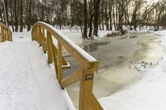 Unmoving frozen river underneath wooden bridge. Unmoving frozen snowy river underneath wooden bridge with railing visible. River plants also frozen into water stock image