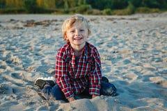 unny微笑的笑的白色白种人儿童孩子白肤金发的男孩,坐的使用与在海滩的沙子在日落 库存照片