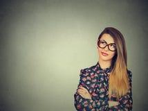 Unny förvirrad ung skeptisk kvinna i exponeringsglas som tänker att se upp Royaltyfria Bilder