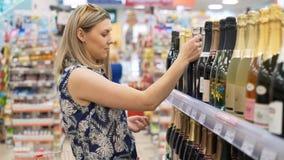 Uno blondy busca el champán en minimarket almacen de metraje de vídeo
