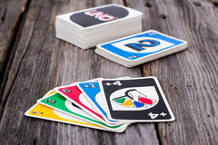 Uno card game on wood table. Sorel-Tracy, Canada - January 13, 2016: view of Uno card game on old wood table. The game was developed by Merle Robbins in Ohio stock photography